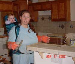 7-month-old Sara on my back while I grouted the kitchen tile of our new kitchen, March 17, 2002